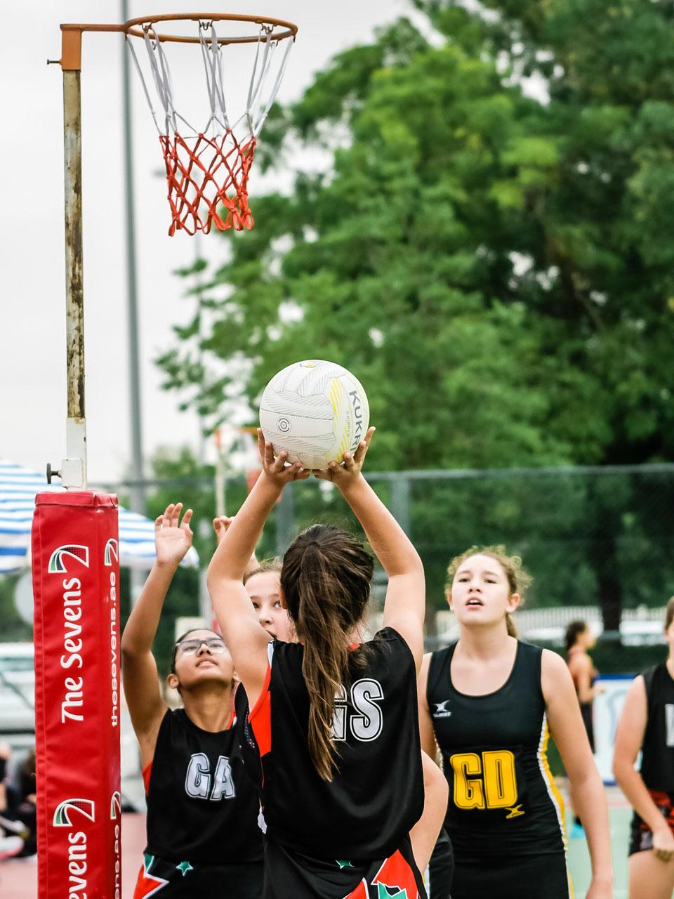 Girl shooting a netball at the Sevens